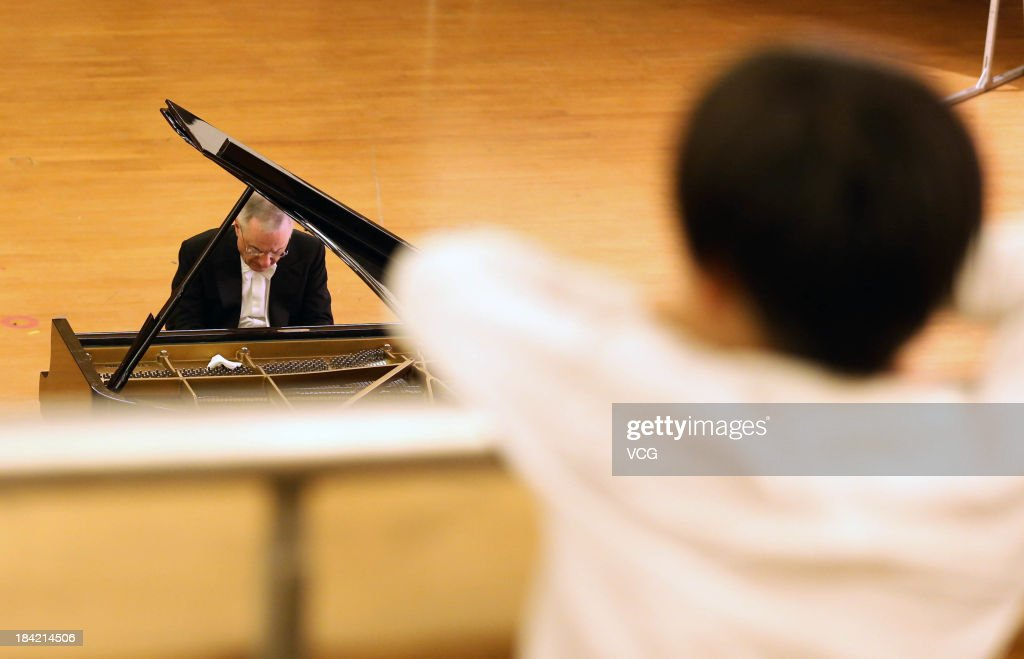A blind boy listens as Italian pianist Michele Campanella performs on the stage during the Jiangsu International Piano Master Music Festival at Nanjing University of the Arts on October 11, 2013 in Nanjing, China.