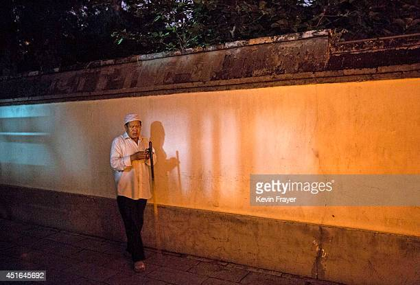 A blind Chinese Muslim of the Hui ethnic minority leaves after breaking fast during the holy fasting month of Ramadan at the historic Niujie Mosque...