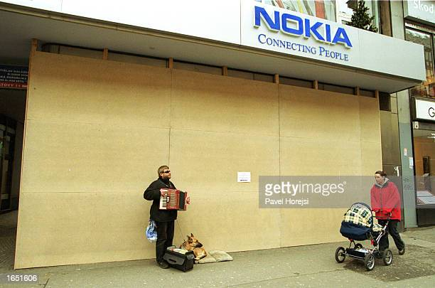 A blind entertainer plays his accordion in front of a boarded up Nokia store November 20 2002 in central Prague Czech Republic The city is bracing...