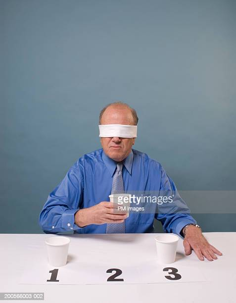 Blind folded middle aged man taking taste test, holding one of three cups