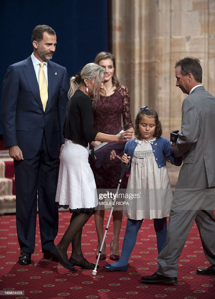 Blind girl Liv Parlee Cantin receives a medal for the Spanish National Organization for the Blind (ONCE) from Spain's Crown Prince Felipe (L) and his wife Letizia, during an official audience at the Reconquista Hotel of the northern Spanish city of Oviedo on October 25, 2013.