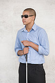 Blind teenage boy wearing sunglasses and holding a cane