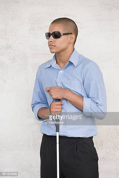 Blind high school student wearing sunglasses and holding a cane