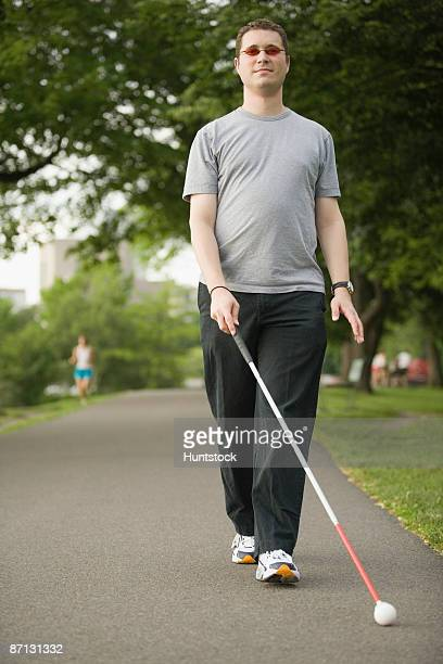 Blind man walking on a walkway with a blind person's cane