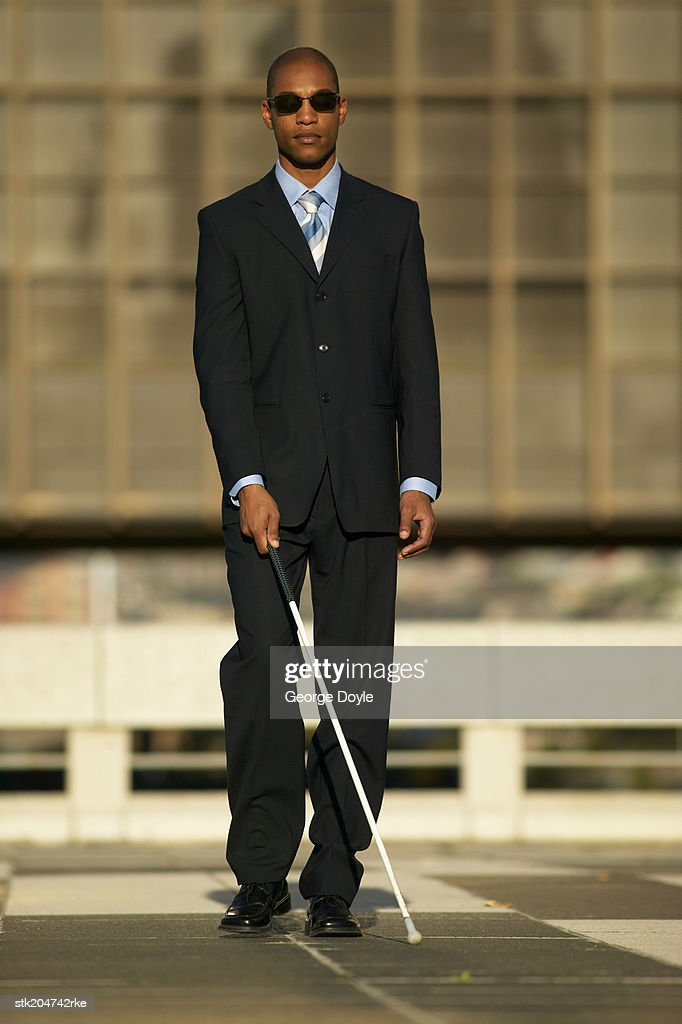 blind man walking with the aid of a white stick