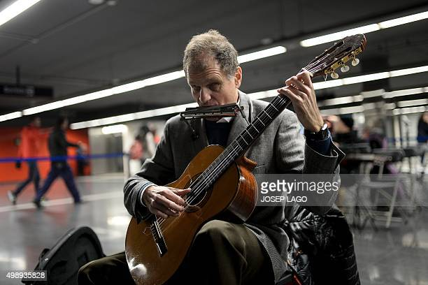 A blind musician performs with an hamonica and a guitar in a Barcelona subway station during the twelfth edition of the suitability test for...
