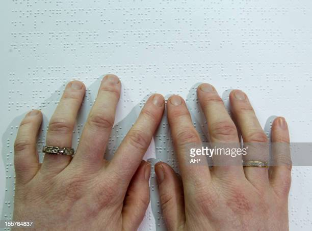 A blind person reads a book written in braille in a book club in Palma de Mallorca on November 7 2012 AFP PHOTO / Jaime REINA