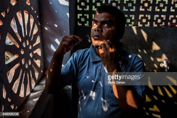 A blind student shaves in dappled light in the bathroom in the hostel residence of the Vivekananda Mission Asram school for the blind This is the...