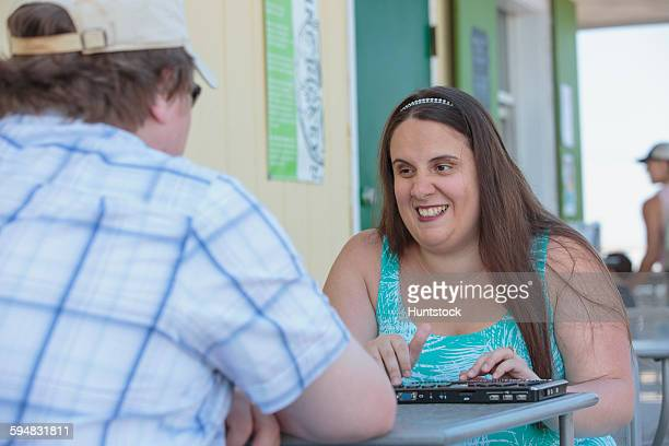 Blind woman using her assistive technology while at a cafe with her fiance
