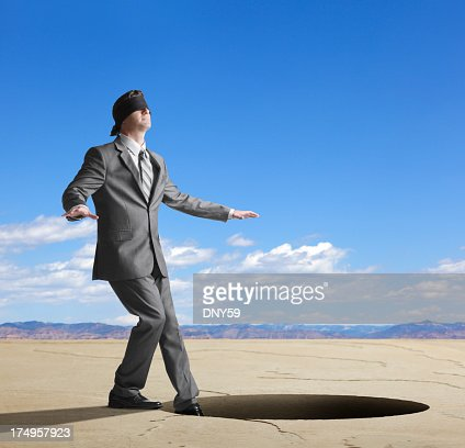 Blindfolded businessman about to step into large hole
