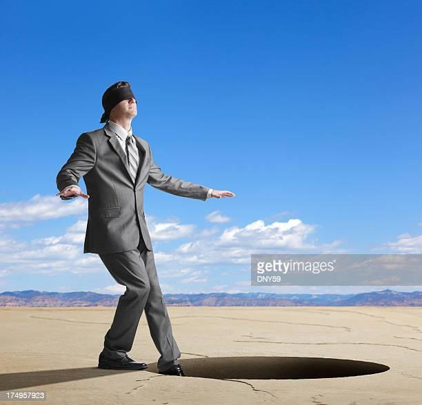 Mit verbundenen Augen Geschäftsmann über zu Schritt in großer Loch