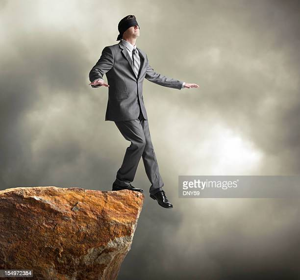 Blindfolded businessman about to step off of a cliff