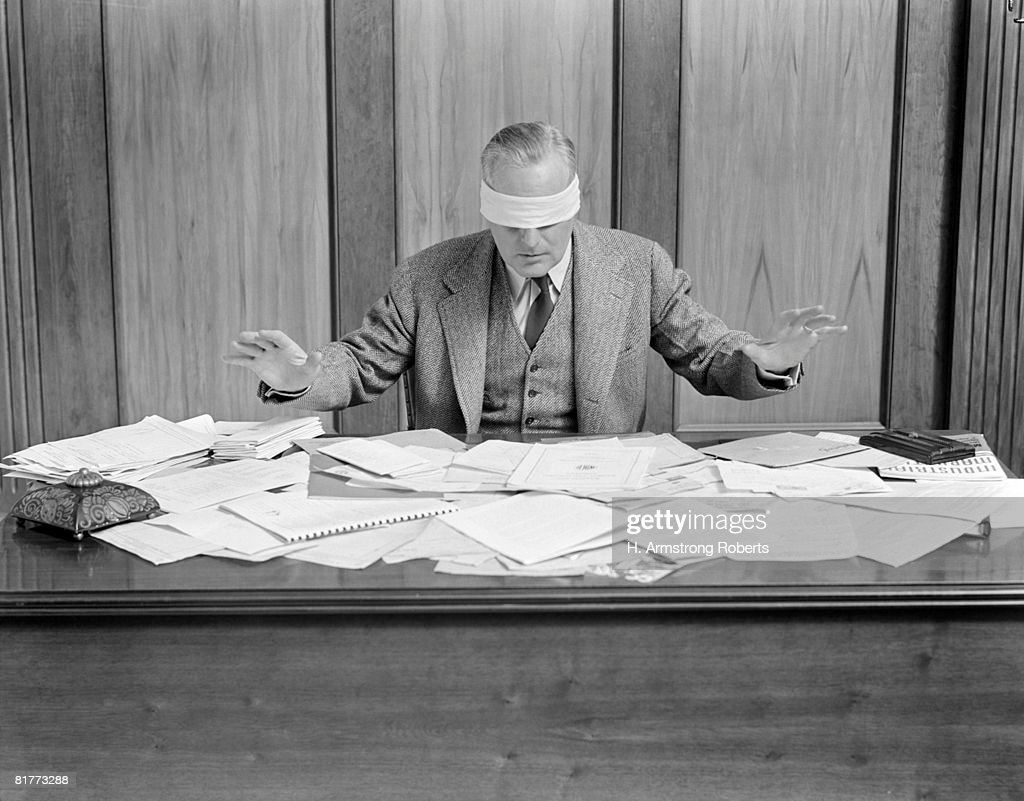 Blindfolded Businessman At Desk Covered With Papers. : Stock Photo
