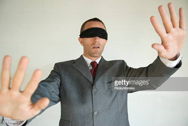 Blindfolded Businessman Blunders Forward With Hands Out