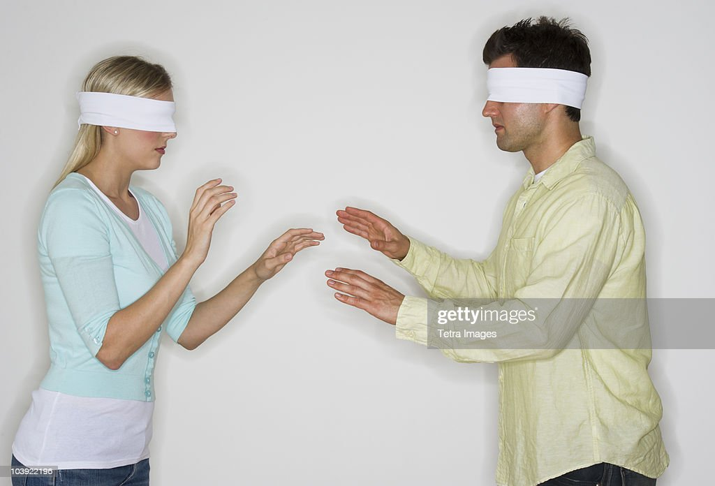 Blindfolded couple looking for each other