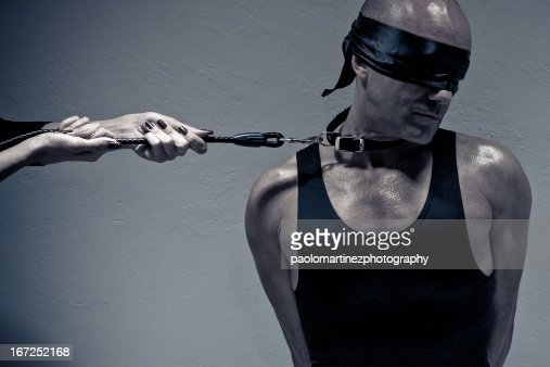 Blindfolded man on a leash by female hands