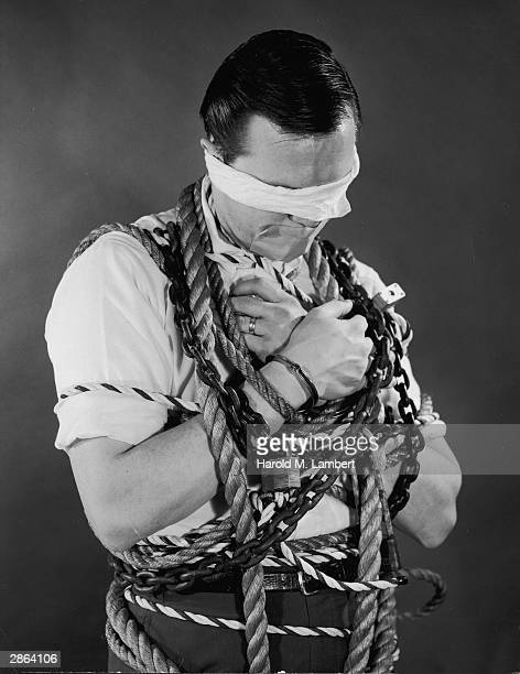 A blindfolded man with his mouth covered by tape stands bound by chains ropes locks and a pair of handcuffs 1950s