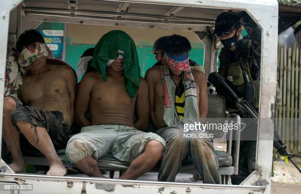 Blindfolded suspected selfstyled Islamic State group members are transported in a police vehicle after being captured in a village in Marawi City on...