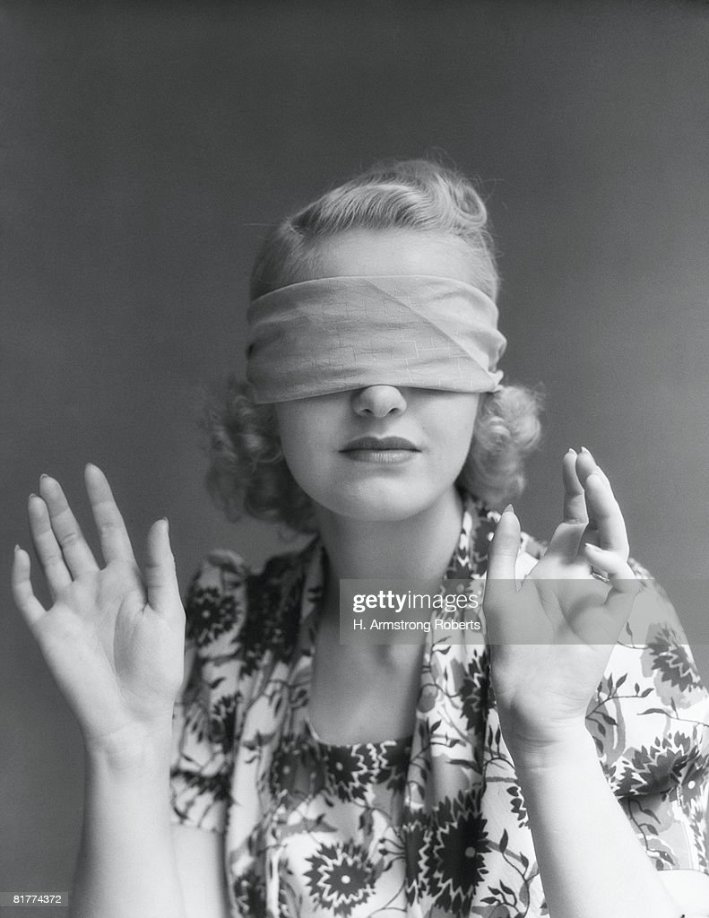 Blindfolded woman holding hands out in front of herself. (Photo by H. Armstrong Roberts/Retrofile/Getty Images) : Stock Photo