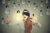 Blindfolded young woman walking through lightbulbs searching bright idea