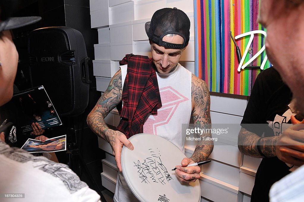 Blink-182 drummer <a gi-track='captionPersonalityLinkClicked' href=/galleries/search?phrase=Travis+Barker&family=editorial&specificpeople=213206 ng-click='$event.stopPropagation()'>Travis Barker</a> signs autographs for fans at the launching of the One Life One Chance web store on December 1, 2012 in Los Angeles, California.