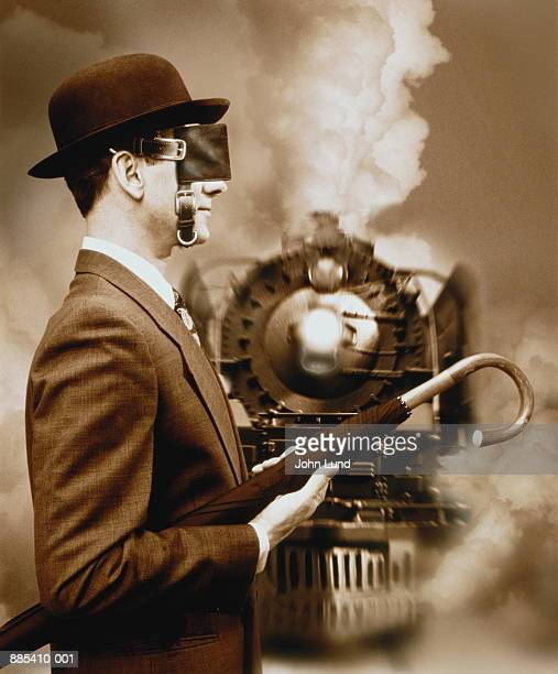 Blinkered businessman on railway, train approaching (Composite)