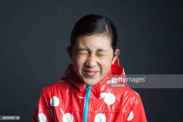 Blinking Asian girl wearing raincoat