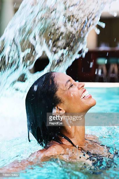 moment de bonheur que généreuse femme de touches sous la cascade de la piscine