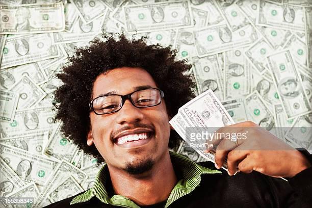 Herrlich glücklicher junger Mann mit viele-Dollar