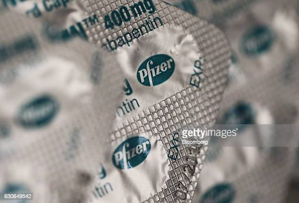 A blister pack containing Neurontin antiepileptic capsules produced by Pfizer Inc sits on a pharmacy counter in this arranged photograph in London UK...