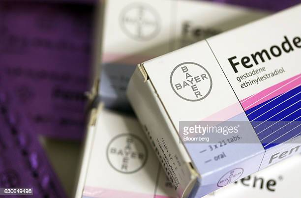 Blister packs containing Femoden oral contraceptive tablets produced by Bayer AG sit on a pharmacy counter in this arranged photograph in London UK...