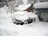 Truck and home covered in deep snow during a blizzard.