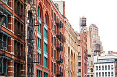 Block of buildings with fire escapes and water towers in Soho Manhattan, New York City