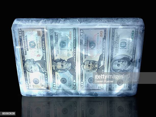 Block of ice encasing US paper currency