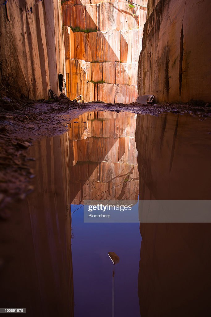 A block of marble is reflected in rainwater at the base of a quarry pit operated by Bloco B in Bencatel, Vila Vicosa, Portugal, on Wednesday, April 17, 2013. Portugal is posting its first trade surplus in at least six decades, which may help vindicate a strategy of front-loading austerity to deliver economic reform. Photographer: Mario Proenca/Bloomberg via Getty Images