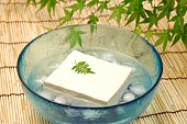 Block of tofu being chilled in icy water