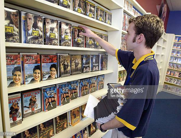 Blockbuster employee Mat Wangrow arranges DVD's on a shelf inside a Blockbuster Video store January 6 2003 in Park Ridge Illinois Walt Disney Co is...
