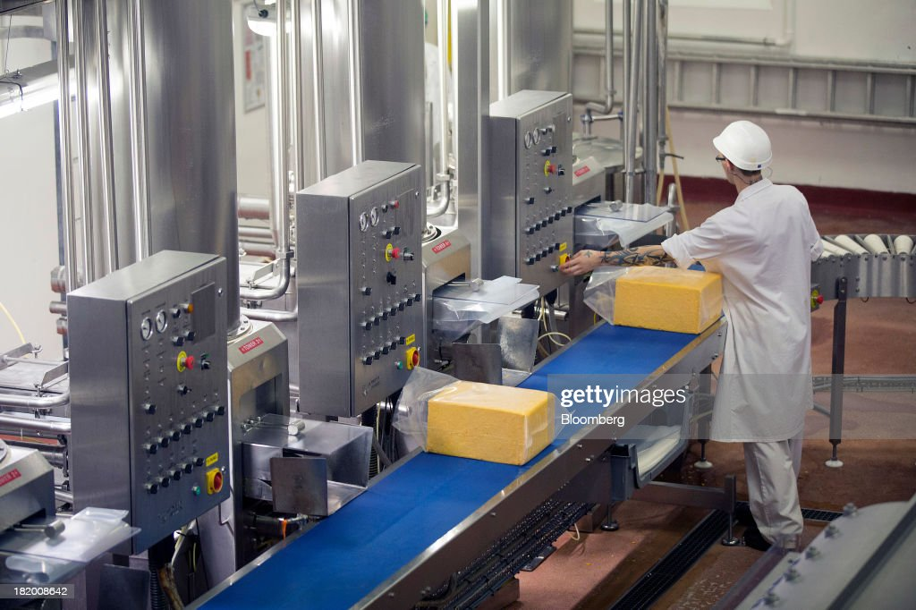 Blocks of Red Leicester cheese move along the packaging line at Wyke Farms Ltd., in Bruton, U.K., on Friday, Sept. 27, 2013. Wyke Farms, the U.K.'s largest family-owned cheese maker and milk processor, has started using waste from its cows and pigs to generate clean power and help shave as much as 1 million pounds ($1.6 million) a year off its energy bills. Photographer: Simon Dawson/Bloomberg via Getty Images