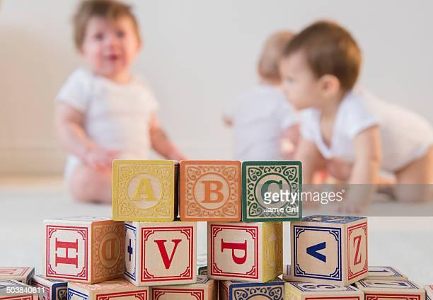 Blocks spelling ABC, babies in background