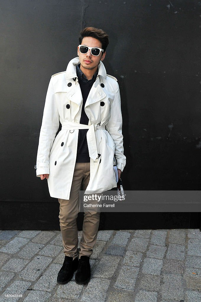 Blogger Ronan Summers wearing Burberry trench coat, Top Shop shirt, Tommy Hilfiger v necked sweater, Top Man trousers, accessorised with bespoke Retrosuperfuture sunglasses from Italy with Carl Zeiss lenses, and Top Man boots at London Fashion Week Fall/Winter 2013/14 on February 18, 2013 in London, England.