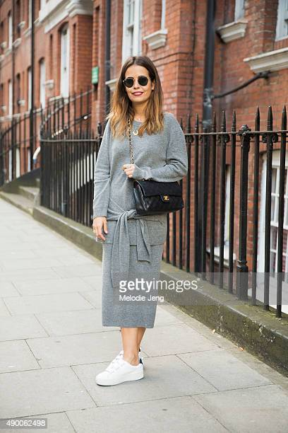 Blogger Sara Escudero of Collage Vintage wears a gray Sandro cashmere sweater with a knottedwaist a gray Sandro cashmere skirt black Chanel purse...