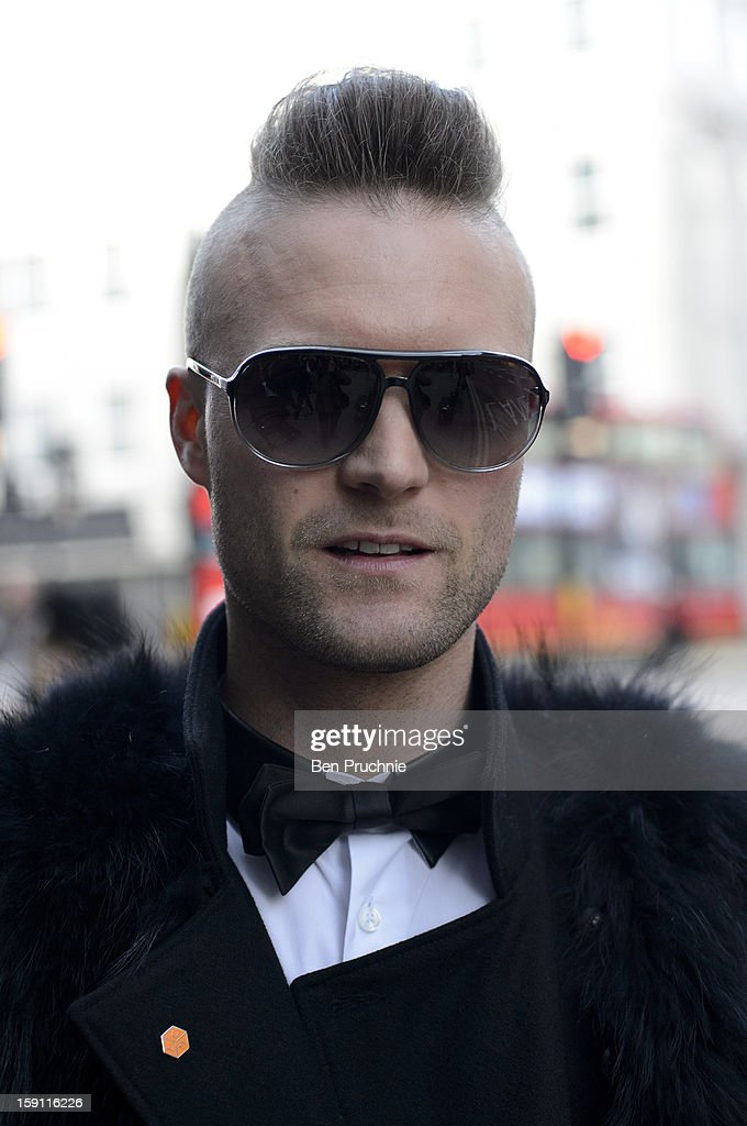 Blogger Thomas (27) poses wearing Prada glasses, H+M bow-tie, a Zara Shirt, River Island Coat, Hotel Paducah fur, Zara bands and Dolce and Gabbana shoes at the YMC Catwalk show during London Collections: MEN on January 8, 2013 in London, England.