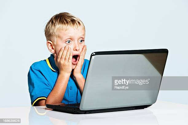 Blond 9 year old boy is shocked by laptop image