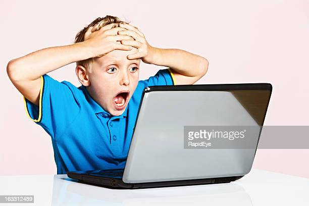 Blond 9-year-old boy is shocked by something on his laptop