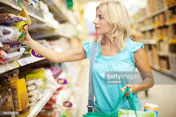 Blonden attraktive Frau Einkaufen Lebensmittel im Supermarkt.