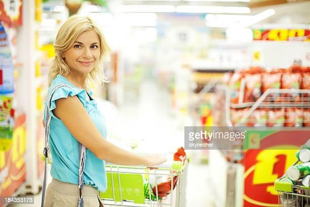 魅力的な金髪の女性のスーパー食材を購入します。