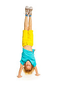 8 years old boy standing on hands upside down isolated on white