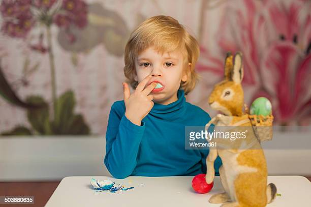 Blond boy with Easter bunny eating egg