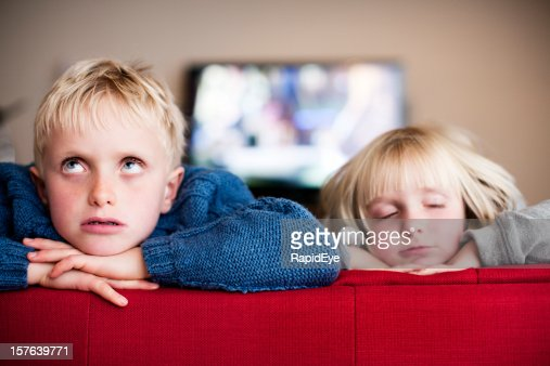 Blond brother & sister sit indoors bored and sleepy