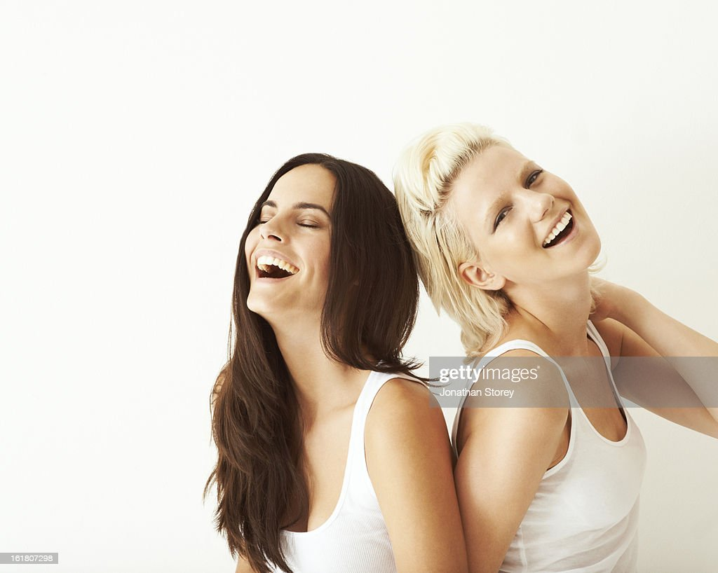 blond & brunette girls laughing together : Stock Photo